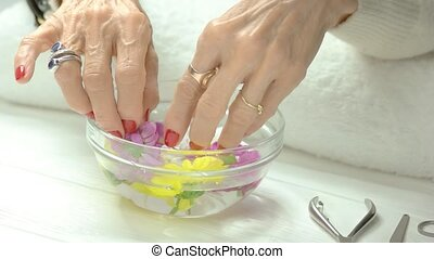 Spa treatment for female hands. Old woman hands take out...