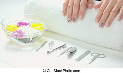 Spa treatment for female hands. Young woman beautiful hands on white towel. Bowl with water and chrysanthemums, manicure instruments. Hands treatment and nails care.