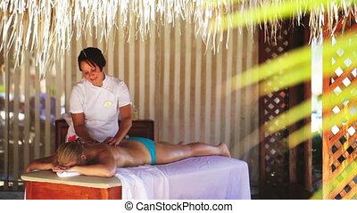 Spa treatment massage in gazebo - Masseur providing spa...