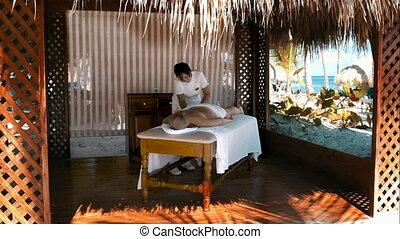 Young blond woman on a massage at a bungalow in the tropics. Latin masse doing massage the neck area of a young blonde in an open bungalow on a background of tropical palms. Blonde girl with a flower in her hair doing a back massage