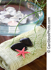 Spa treatment - Bowl of water with candle and rose petals,...