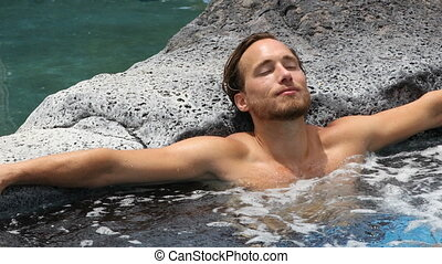 Spa wellness - man relaxing in hot tub whirlpool jacuzzi...