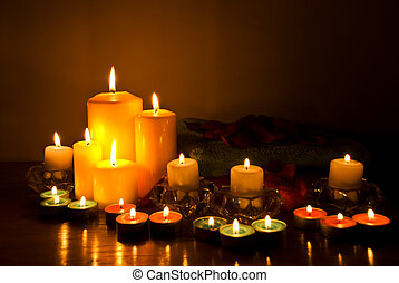 Arrangement for spa with candle lights, towels and petals in darkness on wood table
