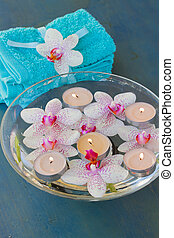 spa with floating orchideas  and candles