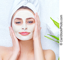 Spa woman applying facial clay mask. Closeup portrait of beautiful girl with a towel on her head applying facial mask