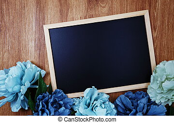 space copy on blackboard with flower decoration top view on wooden background