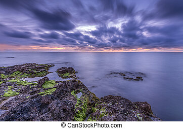 space vivid sunset over the tranquil mild oceanic rocky coastlin