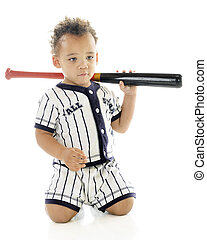 An adorable biracial 2-year-old with a bat over his shoulder, spacing out in his baseball uniform. On a white background.