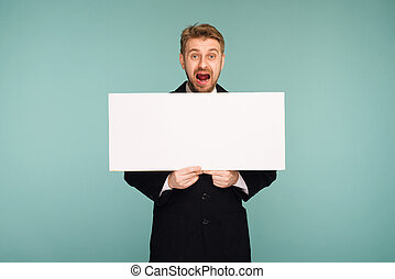 Spacey mature business man showing blank signboard, on blue background