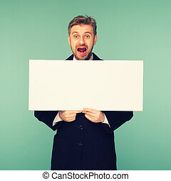 Spacey mature business man showing blank signboard, on blue background. toned