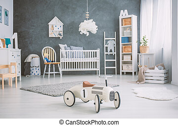 Spacious baby room with white cot, bookcase and dresser