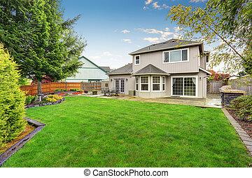 Spacious backyard garden with green lawn and Cozy patio area