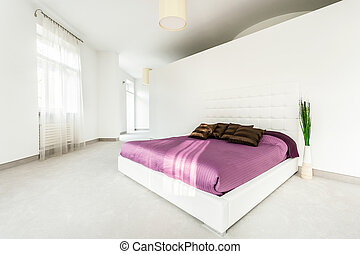 Spacious bed in bright bedroom