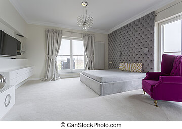 Spacious bedroom interior for marriage and purple armchair