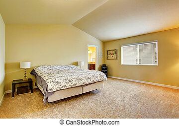 Spacious bedroom interior in beige tones and carpen floor. Northwest, USA