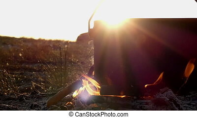 Spacious cauldron stands in a campfire. It boils water at sunset in slow motion