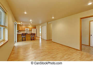 Spacious empty room with hardwood floor connected to kitchen