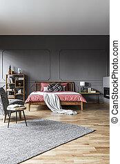 Spacious grey bedroom interior - Wooden table on grey carpet...