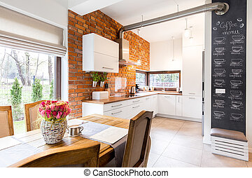 Modern kitchen with big table and garden view