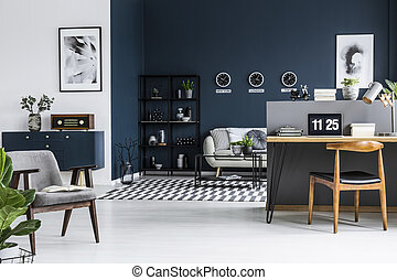 Spacious living room interior with sofa, shelf, retro armchair, blue cabinet and workplace corner with a desk, laptop and chair