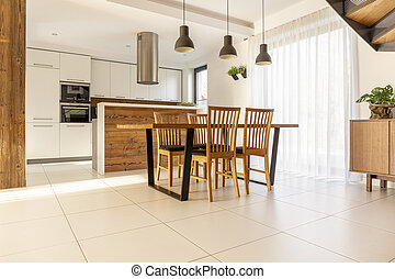 Spacious, open kitchen and dining room with wooden table and chairs, large window, white cupboards and tiles on the floor. Real photo