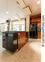Spacious open kitchen with island, wooden furniture and ...