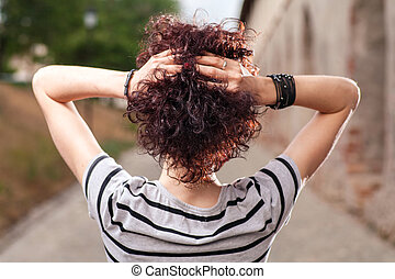 Spacious rear view of a girl with red curly hair