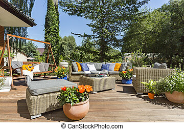 Spacious villa terrace with rattan furniture