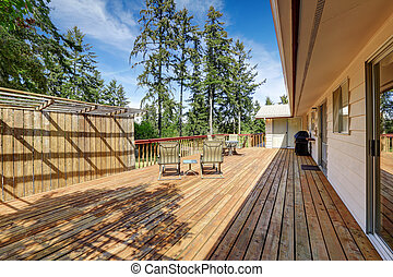 Spacious wooden deck with patio table set.