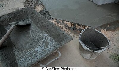 spade and tray with cement mortar on construction site. ...