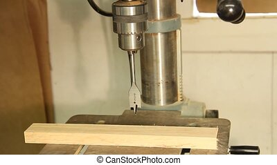spade bit on a drill press drilling a hole in a cabinet board