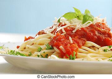 An arranged taller of spaghetti with tomato sauce