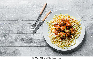 Spaghetti and meat balls on a plate.