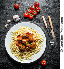Spaghetti and meat balls on a plate with tomatoes and garlic.