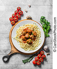 Spaghetti and meat balls on a plate with tomatoes, herbs and garlic.