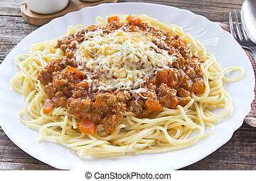 Spaghetti bolognese on plate with fork and spoon