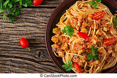 Spaghetti bolognese pasta with tomato sauce, vegetables and minced meat - homemade healthy italian pasta on rustic wooden background. Top view. Flat lay