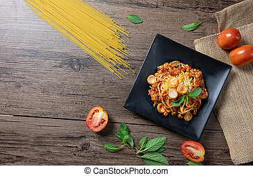 Spaghetti Bolognese with tomato sauce,sausage and basil in black plate on wooden background with copy space.