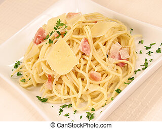 Spaghetti alla Carbonara on a white plate garnished with fresh parmesan cheese and parsley.