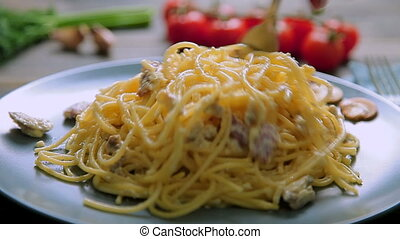Spaghetti Carbonara with ham and mushrooms in blue plate on wooden table