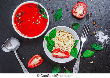 spaghetti in a plate and tomato sauce in a small bowl with spices seasoning basil sauce spoon on a black table. copy space, close up, horizontal orientation, top view, flat lay