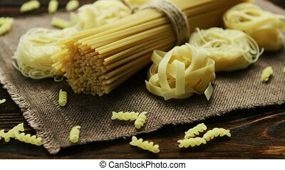 Spaghetti of different kind on napkin - Uncooked macaroni of...
