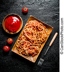 Spaghetti on a plate with tomato sauce in a bowl.