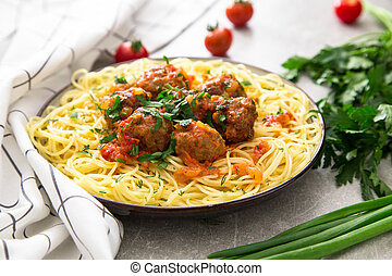 Spaghetti pasta with meatballs and parsley with tomato sauce, selective focus