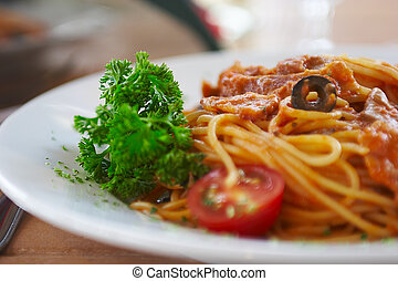 Spaghetti with a tomato sauce on a table in cafe.
