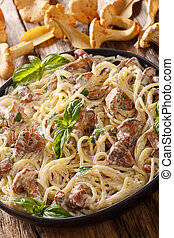 Spaghetti with chanterelle mushrooms in cream sauce with basil close-up on a plate. vertical