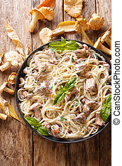 Spaghetti with chanterelle mushrooms in cream sauce with basil close-up on a plate. Vertical top view