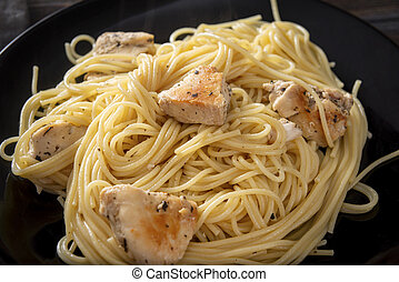 spaghetti with chicken fillet on a black plate ,