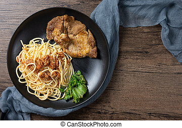 Spaghetti with Grilled black pepper and garlic pork steak in a black plate. top view on wooden background.