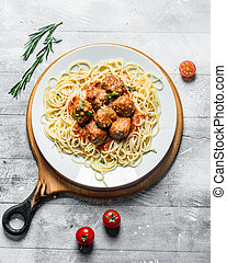Spaghetti with meat balls on a plate of rosemary and tomatoes.